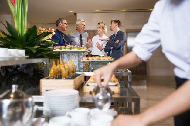 cheerful-business-people-talking-buffet_1262-1720